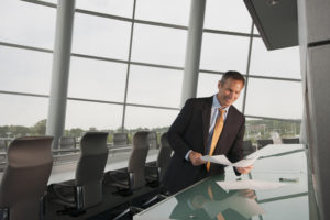 Businessman in office with tables and chairs